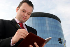 Stupid people try to remember,. Young businessman smiling and taking notes in front of a corporate building Stock Photo