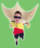 Stupidhero. A kid dressed as a superhero using rubber household gloves, a curtain and mask. Jumping as if taking off in flight. Probably after some baddy Stock Images