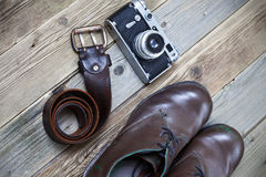 Sturdy brown boots, leather belt, and rangefinder camera Royalty Free Stock Photos