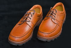 Sturdy brown laced walking shoes. An image of sturdy, laced,  men's brown walking shoes isolated on a black background Stock Photography