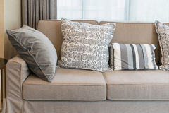 Sturdy brown sofa with grey patterned pillows royalty free stock photography