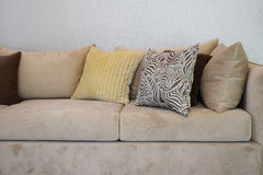 Sturdy brown tweed sofa with grey patterned pillows Stock Images