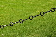 Sturdy chain of iron on a lawn Royalty Free Stock Photography