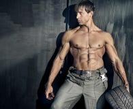 Sturdy guy. Portrait of beautiful sturdy guy with rubber tire on dark  background Stock Photo