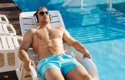 Sturdy man sunbathing near swimming pool. Enjoying the sun. Handsome well-built man lying on a chaise longue near the swimming pool and sunbathing while Royalty Free Stock Photos
