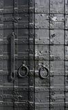 Sturdy metal door. Sturdy black door reinforced with iron plates Stock Photo