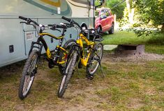 Sturdy mountain bicycles used for exploring nature by the occupants of a motor home. Bikes on kick-stands resting beside an rv parked at a campground in northern Stock Photos