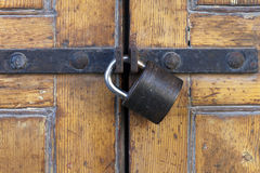 Sturdy padlock on polished wood door Royalty Free Stock Image