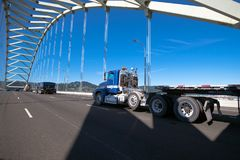 Big rig semi truck with long flat bed trailer running on arched Stock Photo