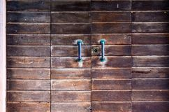 Sturdy wooden door , with large handles oxidized Stock Photography