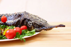 Sturgeon baked with vegetables and greens Stock Photography