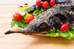 Sturgeon baked with vegetables and greens Royalty Free Stock Image