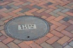 Sturm-Abfluss-Abdeckung auf einer Ziegelstein-Straße Lizenzfreie Stockfotos