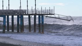 Sturm auf dem Meer Große Wellen stoßen auf dem Pier nahe dem Ufer zusammen stock footage