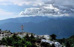 Sturm kommt Frau in der Yogahaltung meditierend in den Bergen Stockbilder