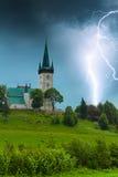 Sturm mit Blitz in der alten Dorfkirche Stockbild