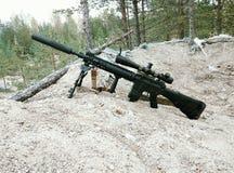 Sturmgewehr auf dem Hintergrund von Kiefernwäldern und -sand Lizenzfreie Stockfotografie
