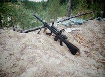 Sturmgewehr auf dem Hintergrund von Kiefernwäldern und -sand Stockfoto