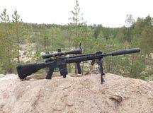 Sturmgewehr auf dem Hintergrund von Kiefernwäldern und -sand Lizenzfreies Stockbild