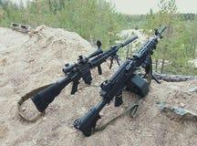 Sturmgewehr und Maschinengewehr auf dem Hintergrund von Kiefernwäldern und -sand Stockfoto
