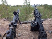 Sturmgewehr und Maschinengewehr auf dem Hintergrund von Kiefernwäldern und -sand Lizenzfreies Stockfoto