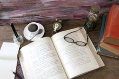 Sturmlaternen-Kaffeetasse der alten Bücher, Kompass, Gläser und Bleistift Stockfotografie