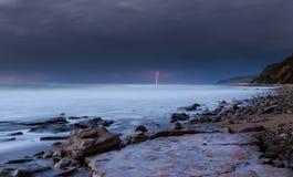 Sturmnähern und -blitz auf dem Strand Stockbild