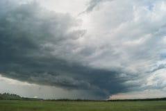 Sturmwirbelsturm über Sommerfeldern, -hügeln und -wäldern lizenzfreie stockbilder