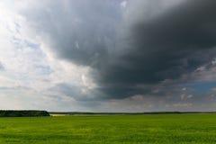 Sturmwolke über einem grünen Feld am Abend Lizenzfreies Stockfoto