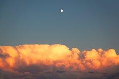 Sturmwolken bei Sonnenuntergang mit Mond Lizenzfreie Stockbilder