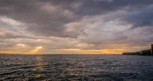 Sturmwolken mit der Sonneneinstellung und Sonnenstrahlen über dem Ozean lizenzfreie stockbilder