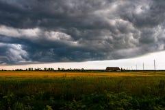 Sturmwolken sind, hängend nähernd und über dem einsamen Häuschen Lizenzfreie Stockfotos