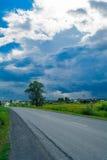 Sturmwolken und blauer Himmel nahe Dorf Stockfotografie