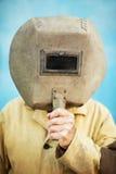 Sturzhelm des alten Schweißers in den Händen des Schweißers lizenzfreie stockfotografie