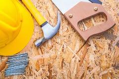 Sturzhelm Handsawhammer und -nägel auf altem hölzernem Stockfotos