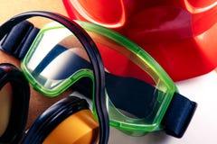 Sturzhelm, Kopfhörer, Schutzbrillen und leeres Papier Lizenzfreies Stockbild