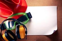 Sturzhelm, Kopfhörer, Schutzbrillen und leeres Papier Lizenzfreie Stockbilder