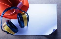 Sturzhelm, Kopfhörer und leeres Blatt Papier Lizenzfreie Stockbilder