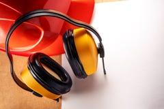 Sturzhelm, Kopfhörer und leeres Blatt Papier Lizenzfreies Stockfoto