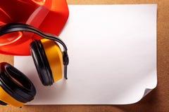 Sturzhelm, Kopfhörer und leeres Blatt Papier Lizenzfreie Stockfotos