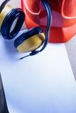 Sturzhelm, Kopfhörer und leeres Blatt Papier Stockbilder