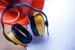 Sturzhelm, Kopfhörer und leeres Blatt Papier Stockfoto