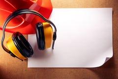 Sturzhelm, Kopfhörer und leeres Blatt Papier Lizenzfreies Stockbild
