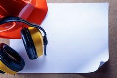Sturzhelm, Kopfhörer und leeres Blatt Papier Stockbild