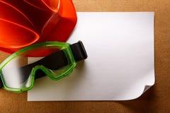 Sturzhelm, Schutzbrillen und leeres Papier Lizenzfreie Stockfotografie