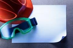 Sturzhelm, Schutzbrillen und leeres Papier Stockfotos