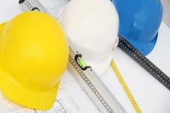 Sturzhelme und Werkzeuge für Bauzeichnungen und -gebäude Stockbild