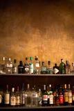 Scaffali di Antivari in pieno delle bottiglie delle bevande alcoliche Immagine Stock