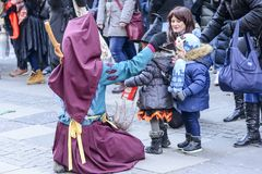 Knelt witch mask plays with childs at Carnival parade, Stuttgart royalty free stock image
