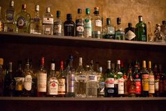 Bar shelves full of alcoholic beverages bottles Royalty Free Stock Image